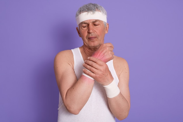 Horizontal shot of senior man dresses white sleeveless t shirt, hurts his wrist during sport training