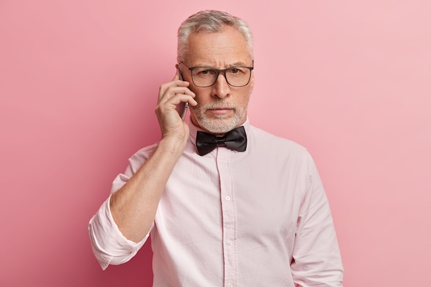 Horizontal shot of senior man talks on phone with serious expression, holds modern mobile phone near ear, has conversation
