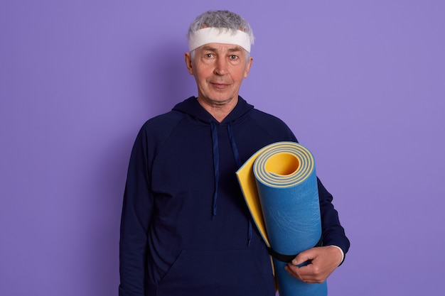 Horizontal shot of senior white haired male with head band and holding blue yoga mat in hands