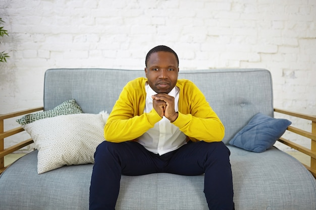 Horizontal shot of serious african american adult male in stylish clothes sitting on gray couch with hands clasped, having pensive facial expression, thinking about something. people and lifestyle