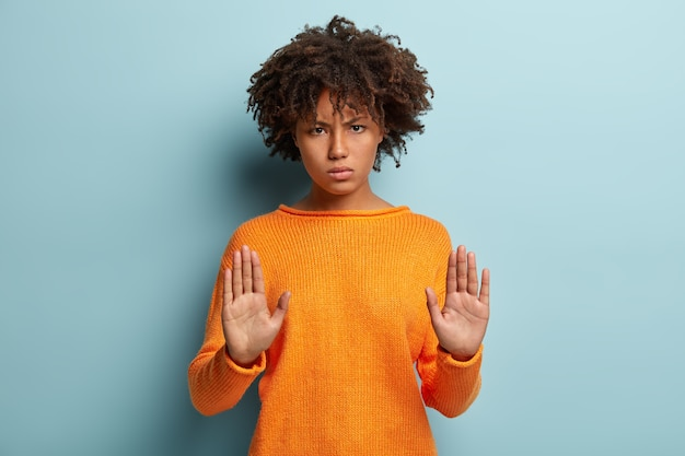 Horizontal shot of serious afro american woman shows stop gesture, stretches palms towards camera, forbids come closer, says thats enough