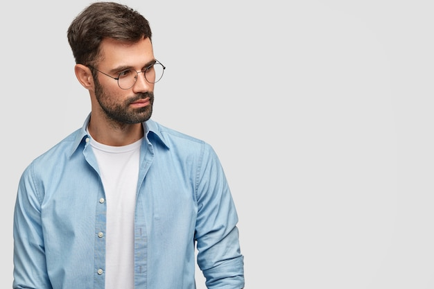 Horizontal shot of serious bearded male focused on something, has pensive expression, looks aside, poses against white blank wall