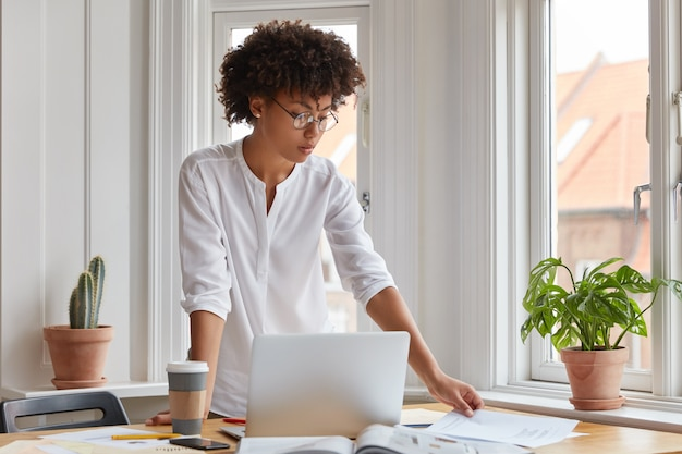 Horizontal shot of serious black young woman stands at desktop