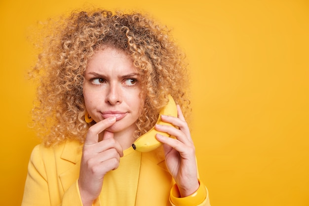Horizontal shot of serious displeased woman concentrated aside holds banana near ear pretends having phone conversation discusses important issues dressed in formal clothes blank space on yellow wall