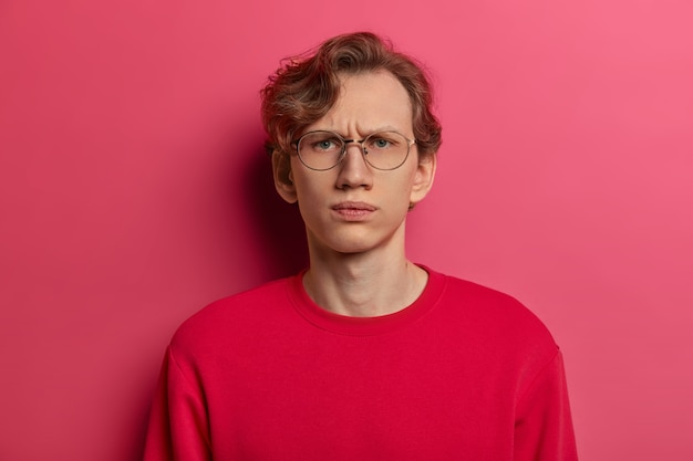 Horizontal shot of serious dissatisfied male model smirks face and looks straightly , doubts he can trust you, wears spectacles and red sweater, isolated on pink wall, feels intense