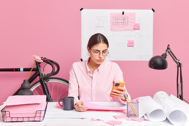 Horizontal shot of serious female student works on architectural project concentrated at smartphone display poses in coworking space analyzes sketh involved in working process makes planning