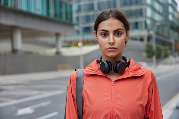 Horizontal shot of serious good looking sportswoman dressed in windbreaker uses wireless headphones returns from workout session after physical activities poses against blurred city