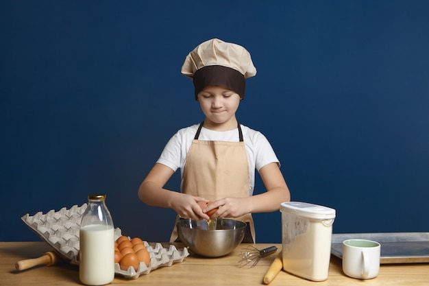 Horizontal shot of serious male child wearing beige apron and hat breaking egg into metal bowl