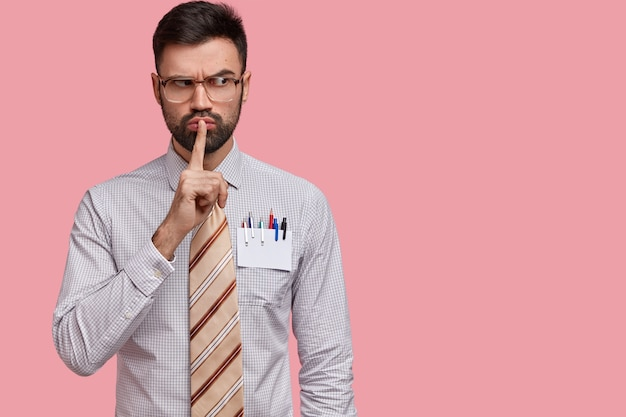 Colpo orizzontale di impiegato maschio serio vestito in camicia e cravatta formale, dimostra il segno di silenzio
