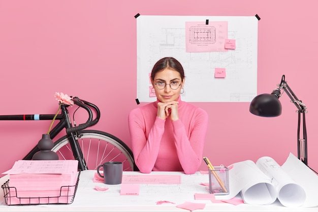 Horizontal shot of serious professional skilled female office worker poses at desktop works on creative task wears casual clothes