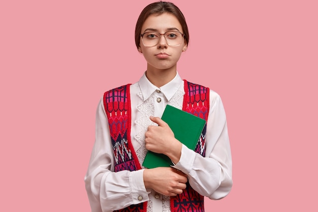 Horizontal shot of serious schoolgirl wonk dressed in old fashionable clothes, spectacles with thick lenses