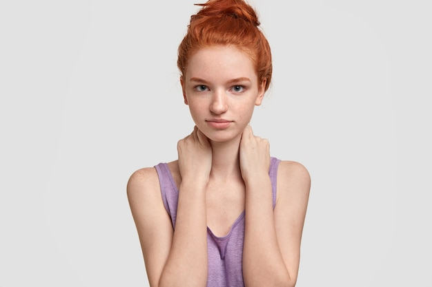 Horizontal shot of serious self confident woman looks directly , keeps hands on neck