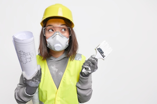 Horizontal shot of serious skilled asian female engineer wears building uniform holds blueprint and paint brush develops construction plan of new building busy with house improvement stands indoor