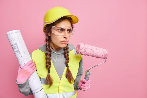 Horizontal shot of serious skilled female engineer focused away with angry expression holds painting roller and blueprint