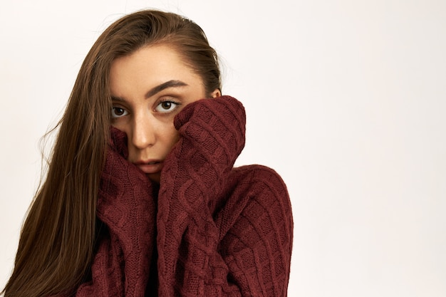 Horizontal shot of serious unhappy young caucasian female wearing knitted jumper with long sleeves, trying to warm up on cold windy winter day, holding hands on her cheeks.