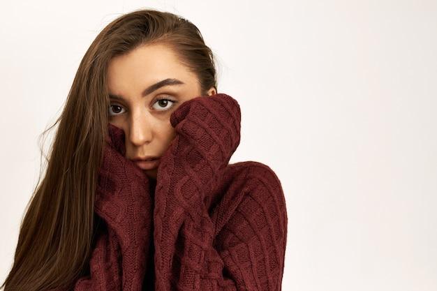 Colpo orizzontale di grave infelice giovane femmina caucasica indossando il maglione lavorato a maglia con maniche lunghe, cercando di riscaldarsi in una fredda giornata invernale ventosa, tenendosi per mano sulle guance.