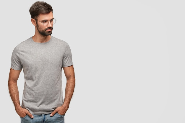 Horizontal shot of serious unshaven male in casual grey t-shirt, keeps hands in pockets, looks aside, thinks about something