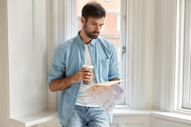 Horizontal shot of serious unshaven man holds printed statistics documents