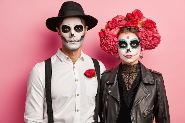 Horizontal shot of serious woman and man dressed in halloween costumes, wear skeleton makeup, wreath made of peonies