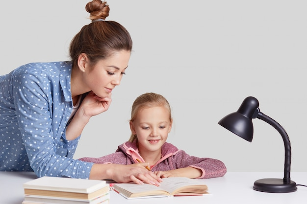 Horizontal shot of serious young mother teaches her small light haired daughter to read, shows something in book, pose at desktop with literature and readinglamp, isolated over white wall