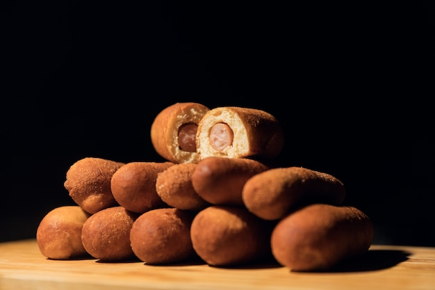 Horizontal shot of several corn dogs with one cut up on a wooden surface