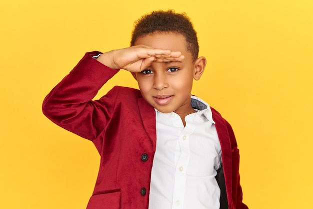 Horizontal shot of sharp eyed curious dark skinned little boy scanning horizon, holding hand on his forehead, gazing into distance, searching for something