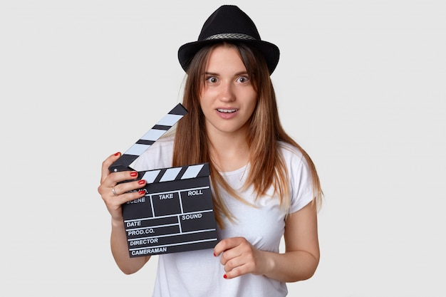 Horizontal shot of shocked beautiful young female film producer holds movie clapboard