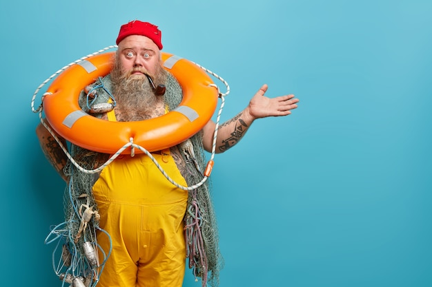 Horizontal shot of shocked embarrassed bearded male seafarer poses with inflated lifering fishing net smokes pipe raises hand over blue wall demonstrates copy space for your advertising content