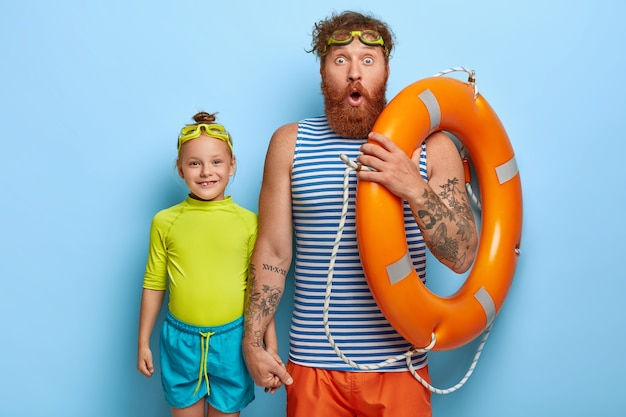 Horizontal shot of shocked father with ginger beard, wears goggles and holds lifebuoy, little female child spends free time with dad, going to learn swimming isolated over blue wall. summer time