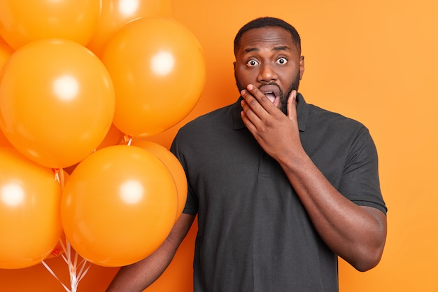 Horizontal shot of shocked man reacts on something with astonished expression holds chin wears casual black t shirt holds bunch of inflated balloons isolated over orange wall
