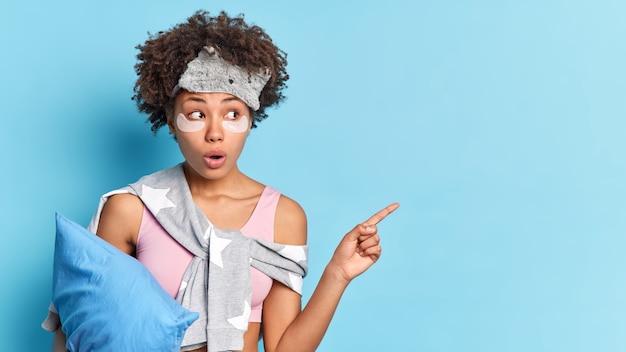Il colpo orizzontale della donna scioccata con i capelli afro vestiti in indumenti da notte applica cerotti di collagene per ridurre il gonfiore tiene i punti del cuscino sorprendentemente lontani isolati sopra il muro blu