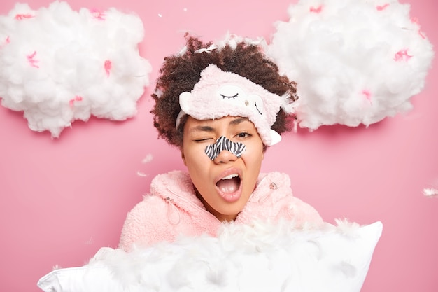 Horizontal shot of sleepy woman yawns as awakes early in morning wears pajama blindfold holds pillow applies nose patch for healthy skin isolated over pink wall clouds above