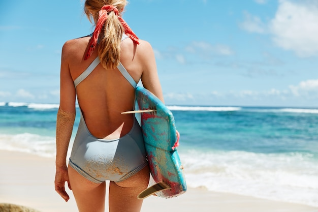 Horizontal shot of slender female in blue bathing suit,  has fit butt holds surfing board, going to have active competitions and hit ocean waves during summer sunny weather.