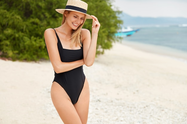 Horizontal shot of slim tall woman wears fashionable swimsuit and hat, has broad smile as spends free time on tropical beach, poses for beauty magazine. people, recreation and sunbathing concept