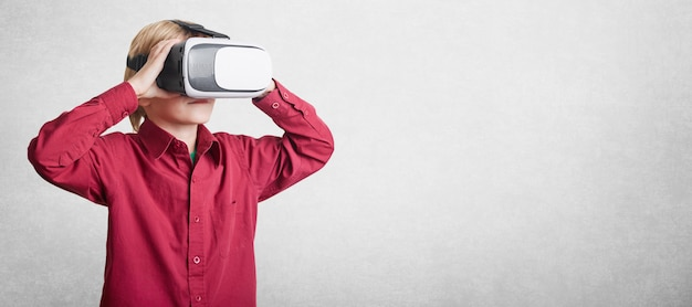 Horizontal shot of small boy wears vr glasses, sees virtual reality, isolated over white wall with copy space for advertising content