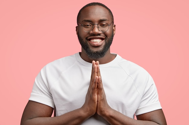 Horizontal shot of smiling black man keeps hands pressed together, believes in something positive