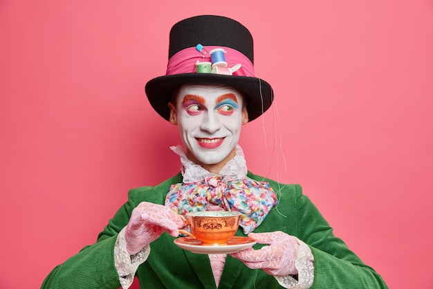 Horizontal shot of smiling cheerful mysterious hatter spends free time on tea party wears hat and costume with bowtie has holiday mood poses against pink wall