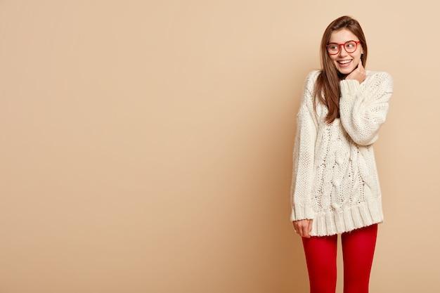 Colpo orizzontale della donna felice sorridente guarda sullo spazio di copia a sinistra, esprime sentimenti sinceri, vede qualcosa di piacevole e divertente, indossa un maglione lavorato a maglia lungo e collant rossi, isolato sul muro beige