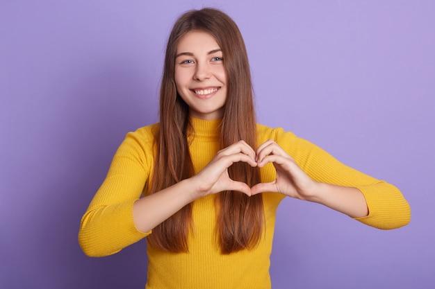 Horizontal shot of smiling woman wearing casual yellow shirt