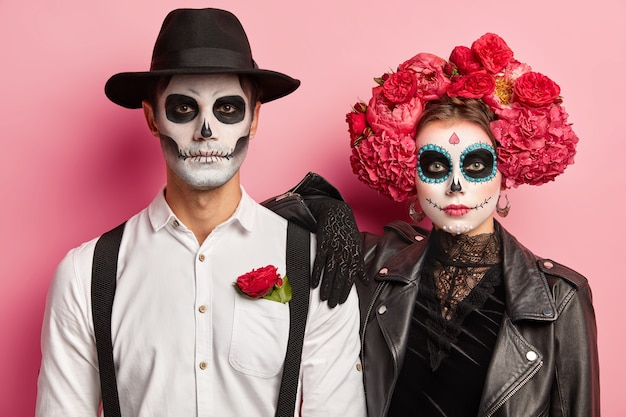Horizontal shot of spooky couple dressed for day of dead in mexico, wear skull masks, stand next to each other, celebrate halloween together, isolated over pink background