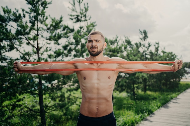Horizontal shot of sporty man with bare chest exercises with elastic expander, gains for strong muscular body, has thick bristle, poses outside. bodybuilder stretches band stands near green trees