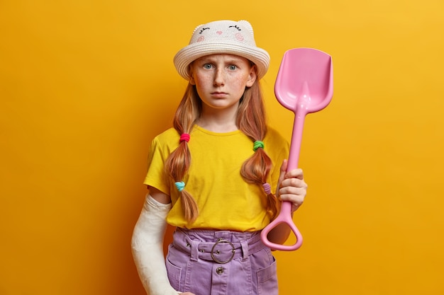Horizontal shot of strict serious redhead girl plays in sand, holds pink plastic shovel, wears fashionable clothes, has broken arm bandaged in cast after doing dangerous sport, isolated on yellow wall
