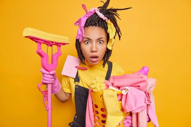 La foto orizzontale di una casalinga stordita con i dreadlocks ha guanti di gomma sulla testa e guarda scioccata