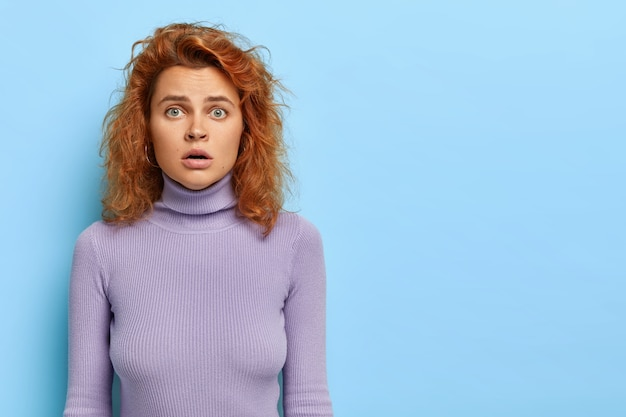 Horizontal shot of stunned woman looks with scary expression, has green eyes and wavy red hair
