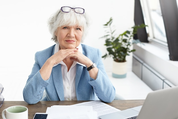 Horizontal shot of stylish elderly female real estate manager wearing nice blue suit and spectacles on her head, clasping hands under chin, having serious confident look, using laptop for work