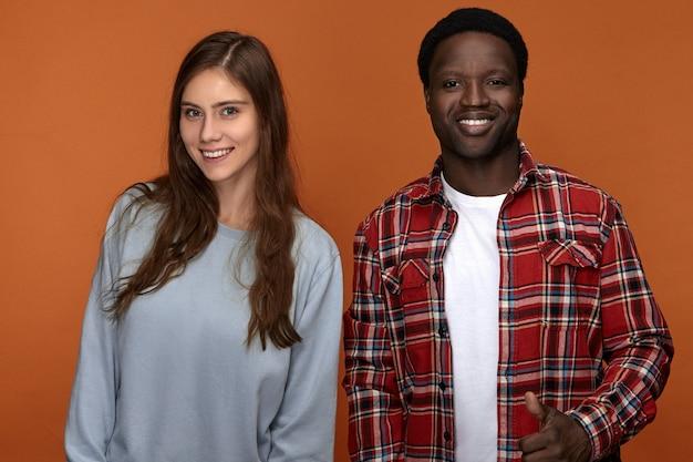 Colpo orizzontale di elegante coppia interrazziale uomo bianco e ragazzo nero felice di stare insieme, in piedi uno accanto all'altro, sorridendo ampiamente relazioni, amore internazionale ed etnia