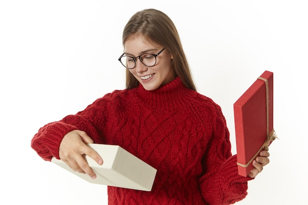 Horizontal shot of stylish joyful young caucasian woman in eyeglasses and knitted sweater having excited happy look while receiving gift for christmas, opening box with present and smiling broadly