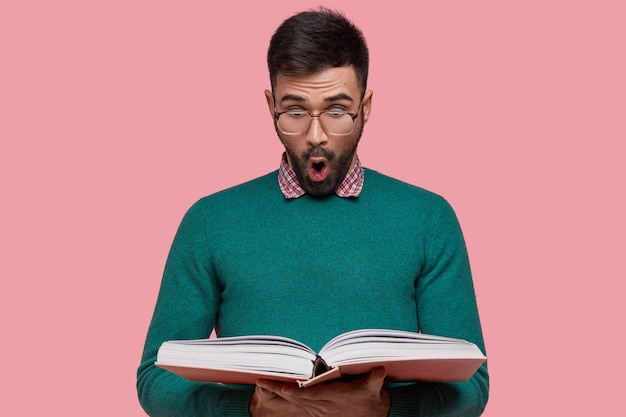 Horizontal shot of surprised bearded young man looks surprisingly at book, find out shocking information