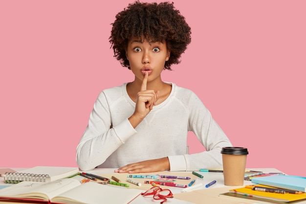 Horizontal shot of surprised dark skinned female illustrator keeps index finger over mouth, demonstrates silence gesture, sits at desktop with notepad, coloured pencils, isolated over pink wall