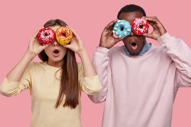 Horizontal shot of surprised dark skinned man covers eyes with delicious sparkling doughnuts, stands near her girlfriend, spend free time together